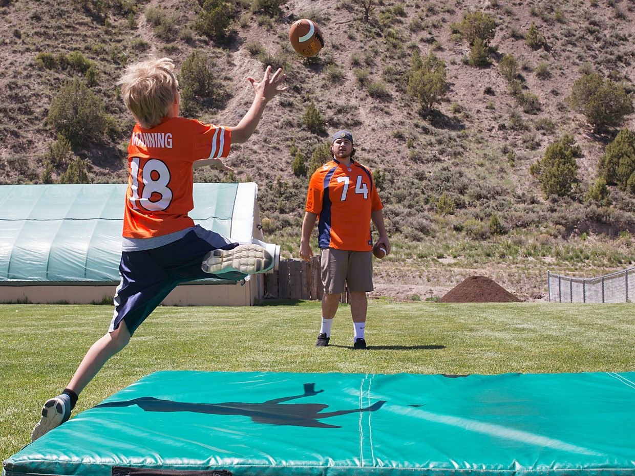 waves a Broncos flag as fans cheer during the Denver Broncos Salute to Fans Tour at Brush Creek Pavilion on Friday. Topor said the flag was waving proudly outside of his house all season long