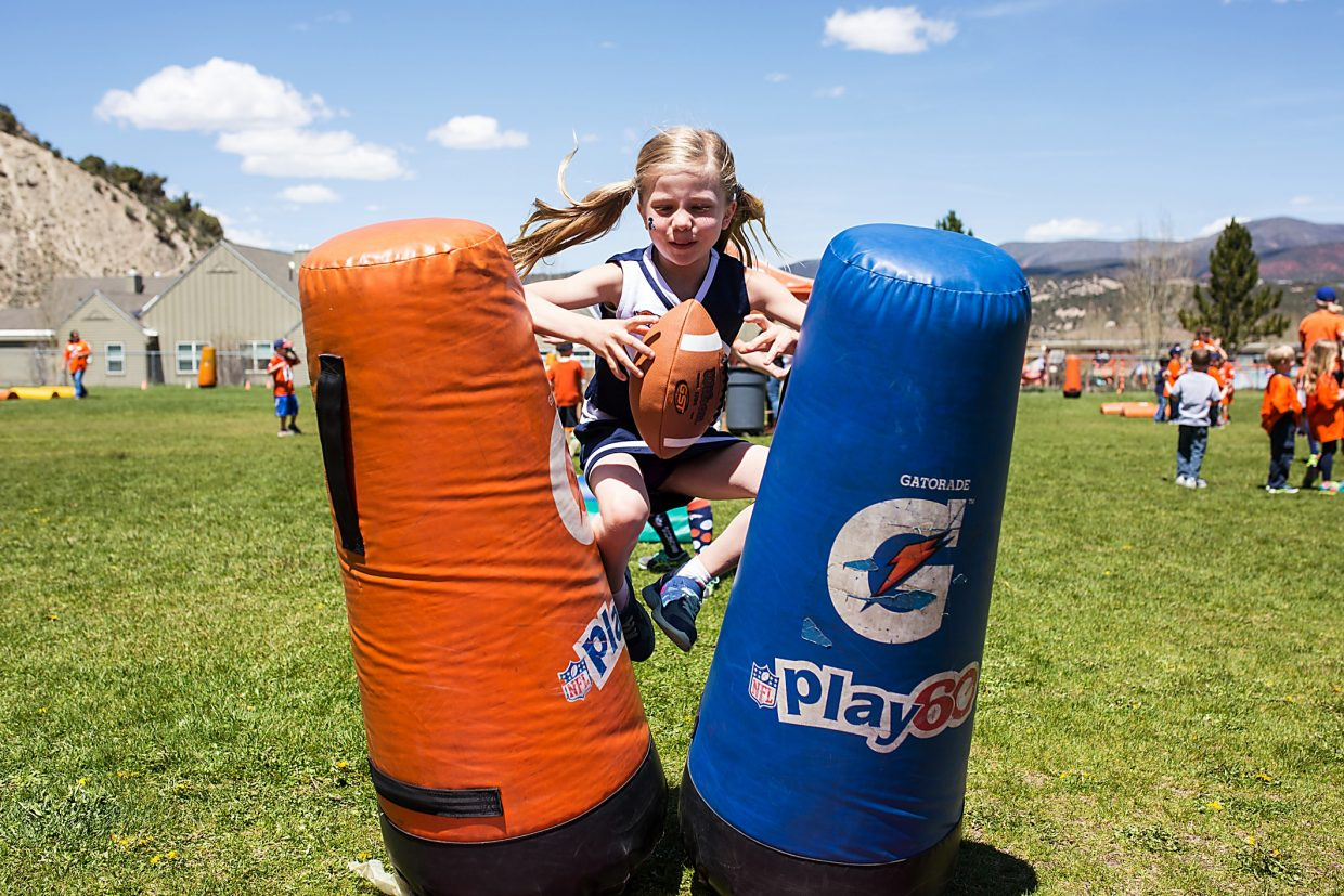 Brush Creek Elementary School student Mason McCormick jumps for a pass thrown by Denver Broncos player Ty Sambrailo during a mini training camp for students in Eagle on Friday.