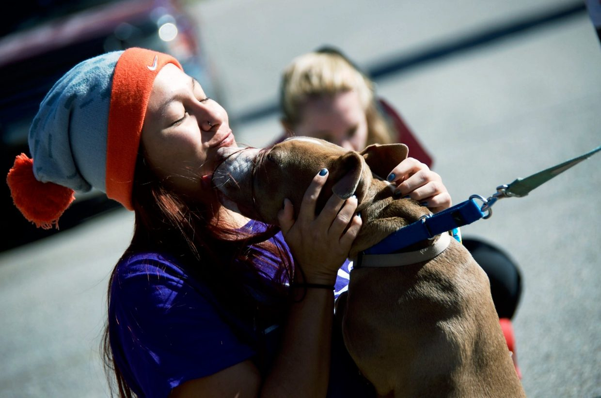 A member of the crowd receives kisses from a dog.