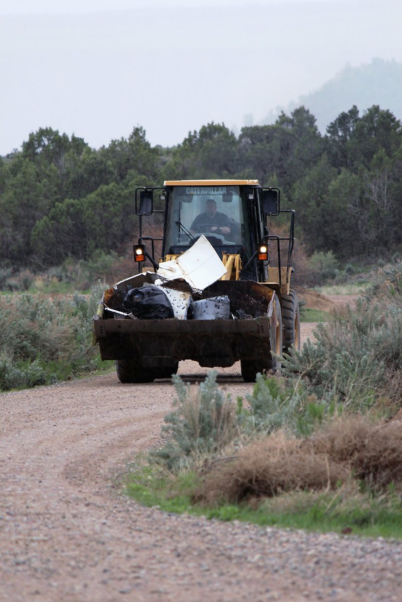throws some scrap metal into a front loader Saturday at the annual Hubbard Mesa cleanup north of Rifle.