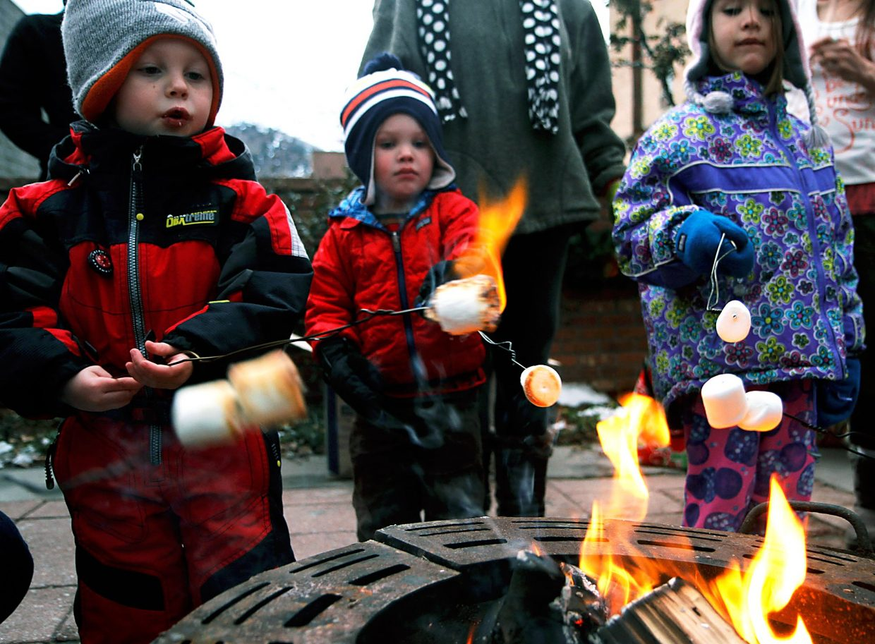 Colby Olson's marshmallow catches fire during Thursday's Day Out Downtown Grand Holiday in Glenwood Springs. Standing next to him is Teagan Lavin and Bella Narvaez.