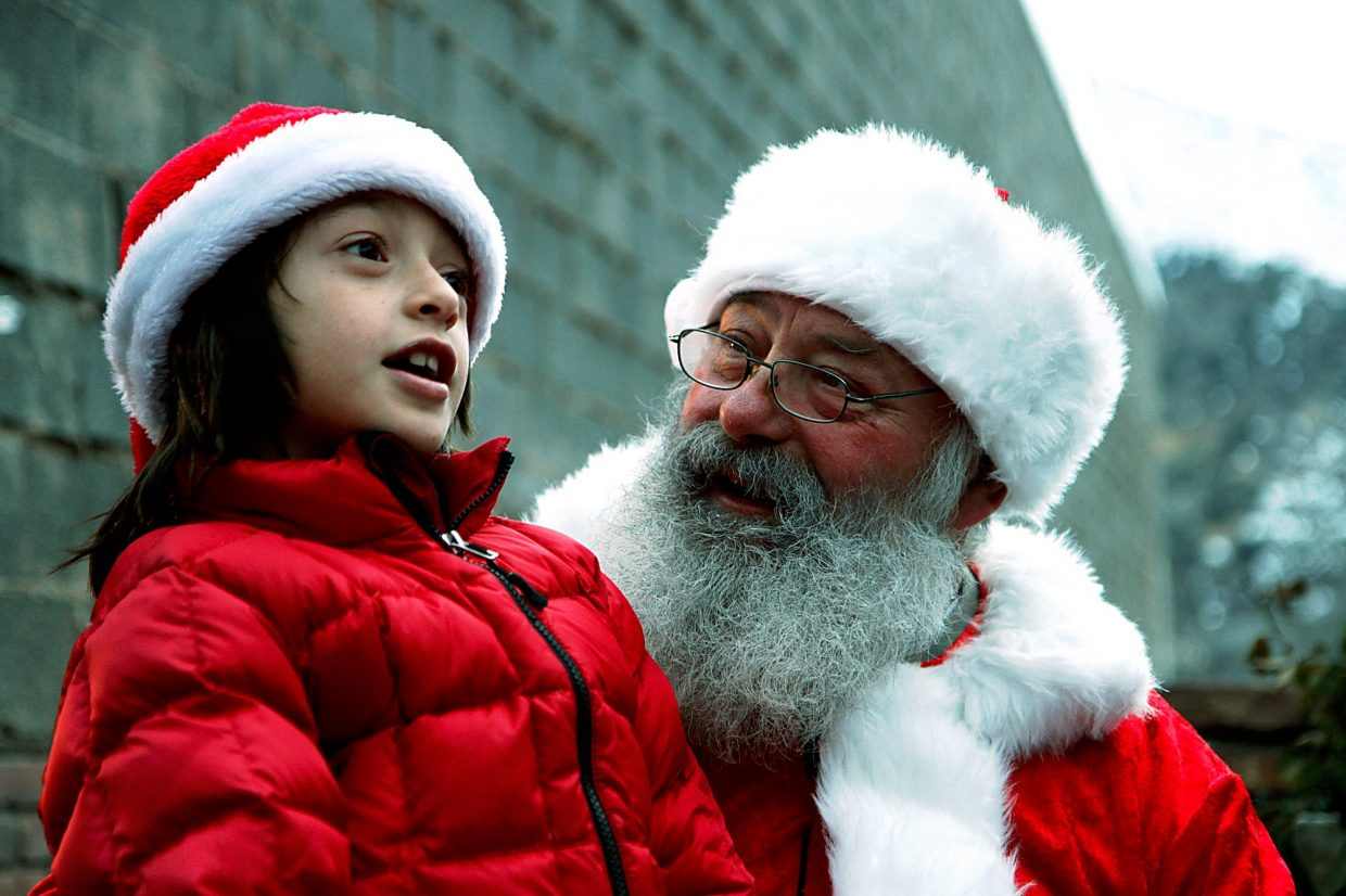 Lesai Loya sits on Santa's lap Thursday during Glenwood Springs' Downtown Day Out Grand Holiday event, which featured Santa and three reindeer. Lesai asked for a cotton candy maker and a remote- control monster truck for Christmas.
