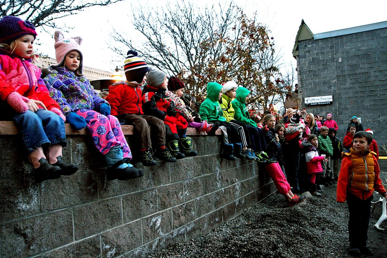 Kids line a wall awaiting the arrival of reindeer at the Day Out Downtown Grand Holiday.