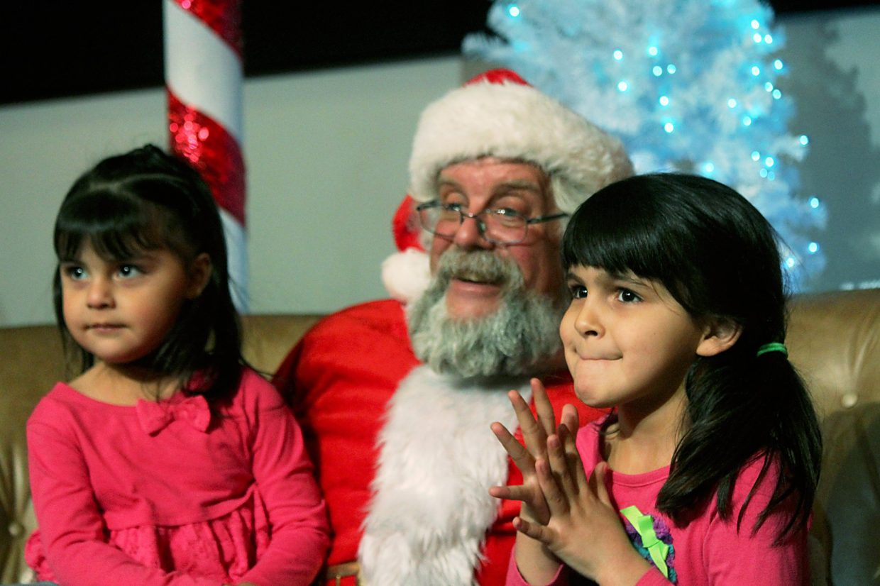Khloe Astorga, left, and Lixcy Gonzalez tell Santa what they want for Christmas.