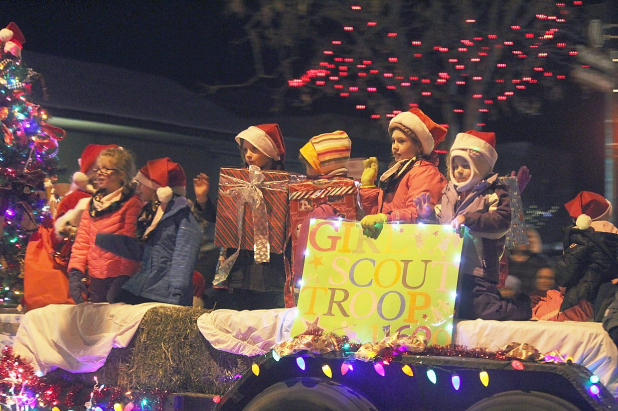 Local Girl Scouts waive to watchers in the 2015 Hometown Holiday Celebration Parade of Lights on Railroad Avenue.