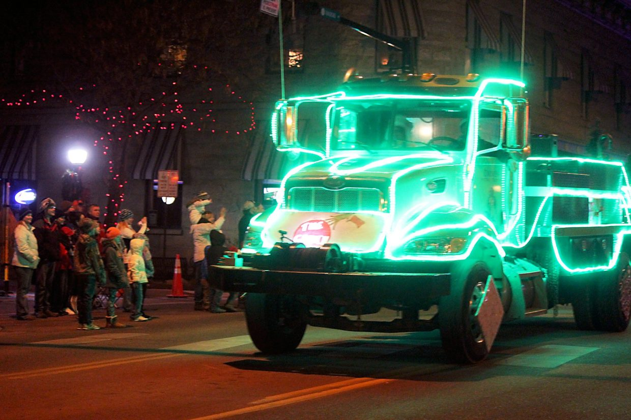 A Grinch-themed truck from Elder Construction, Inc., makes its way down Railroad Avenue.