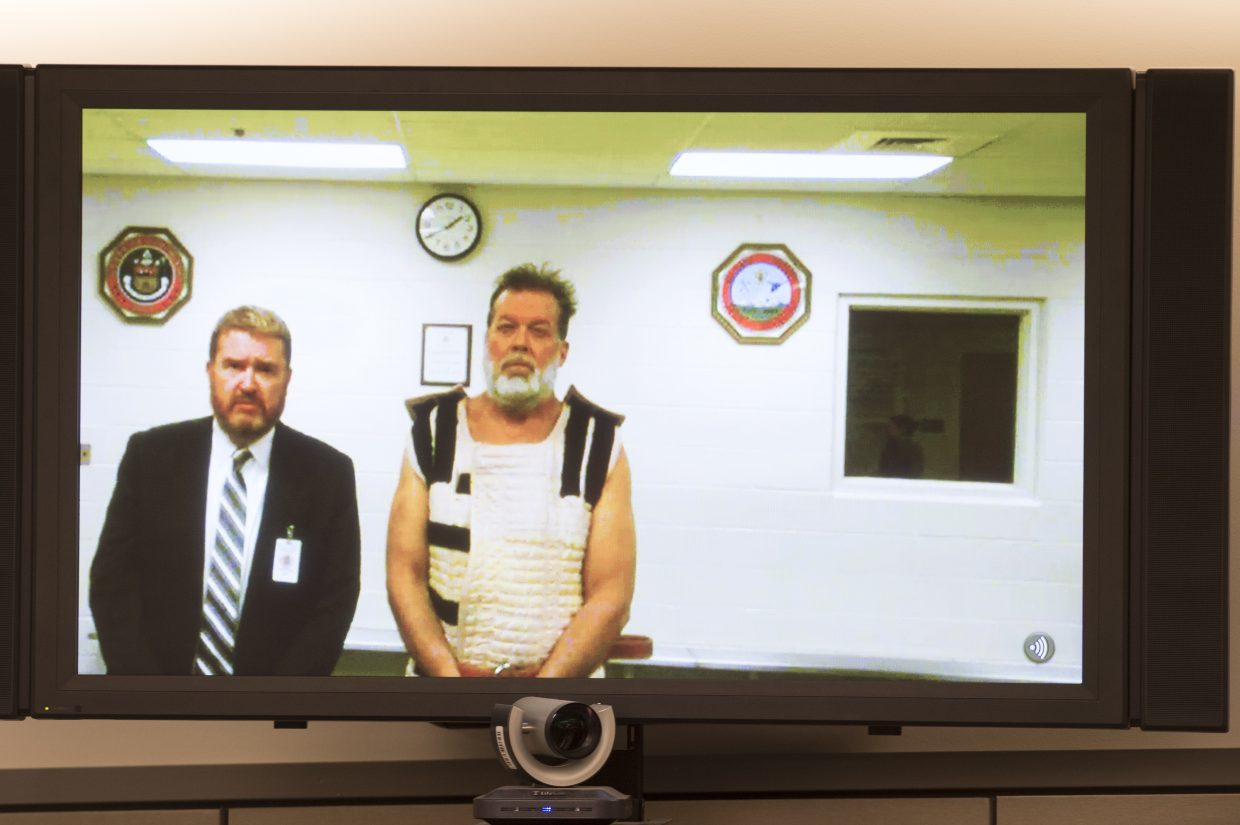 Colorado Springs Planned Parenthood shooting suspect Robert Dear, right, appears via video hearing during his first court appearance, where he was told he faces first degree murder charges, Monday, in Colorado Springs. At left is public defender Dan King.