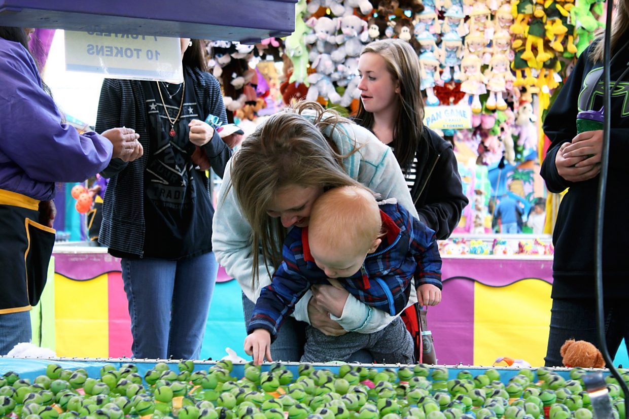 Haven Larrabee, of Silt, holds her son, Declan, as he plucks a rubber turtle from a pool at the 19th annual Rifle Rendezvous.