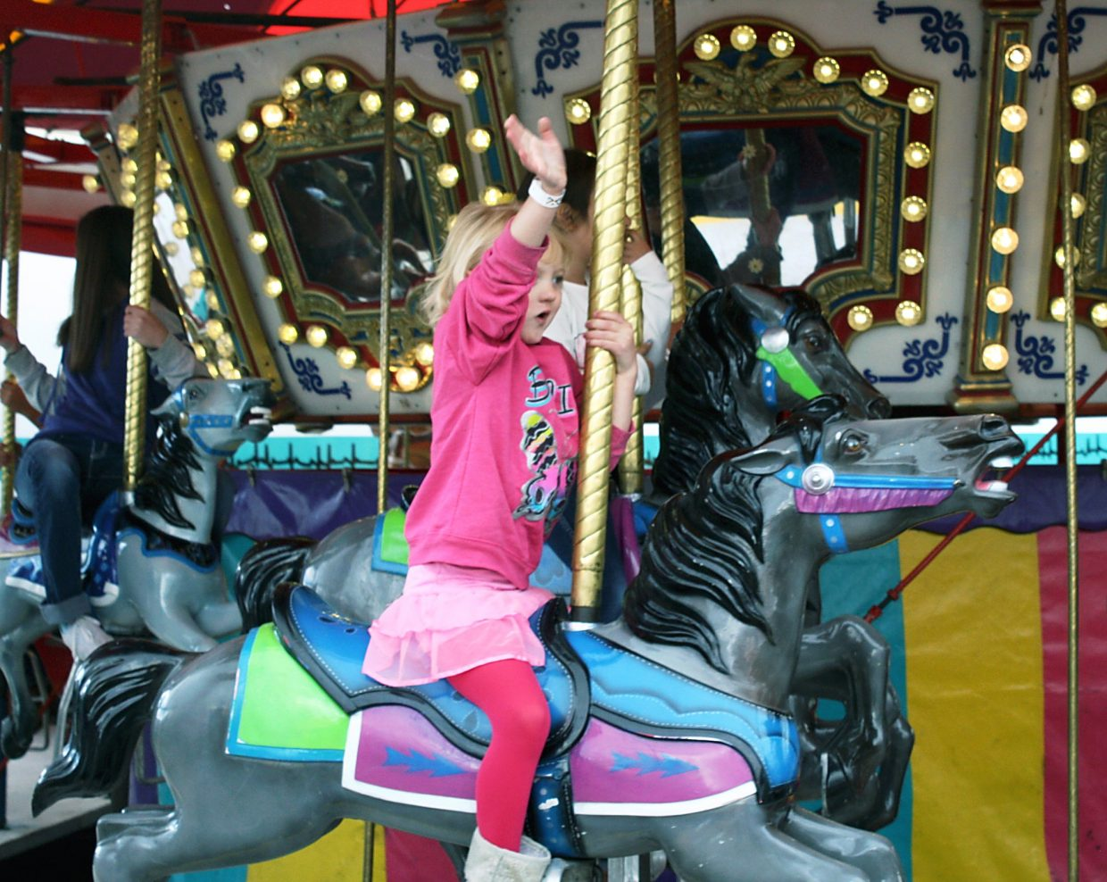 Abigail Morrow waves to her parents during a ride on the merry-go-round at the 19th annual Rifle Rendezvous.