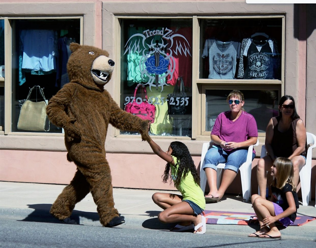 The Rifle Bears mascot stops to high-five Jadah McDaniels, left, and Jaylynne Fusilier during the Rifle homecoming parade Friday on Railroad Avenue.