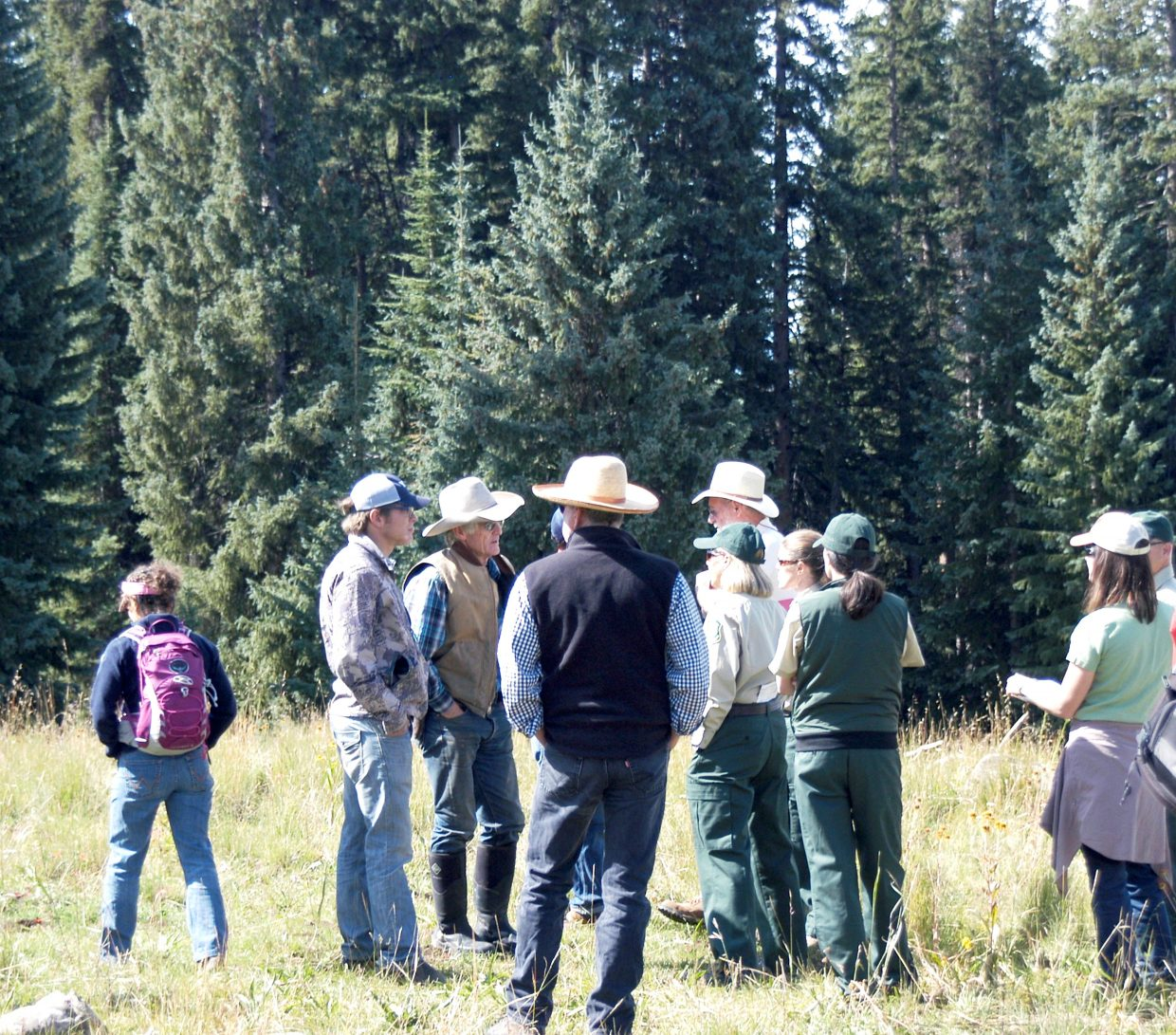 Rancher Bill Fales, centers, asks questions of U.S. Forest Service personnel and others who were on hand for the Tuesday site visit.
