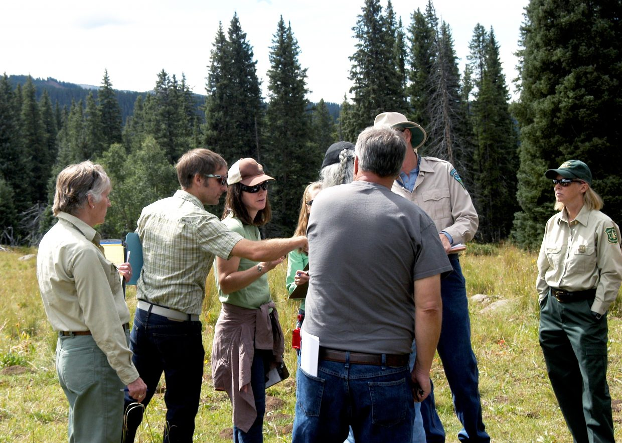 Eric Sanford, second from left, discusses things with Forest Service and BLM officials during the Tuesday site visit to SG's proposed test well site.