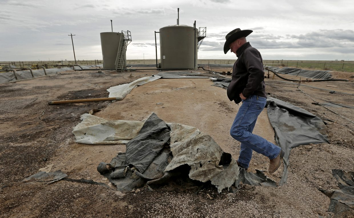 In this April 24, 2015 photo, Justin Johnson looks at a torn lining at a tank and pipeline station adjacent to his ranch near Crossroads, N.M. Trucks bring oilfield wastewater to the station, where it is pumped through pipelines to a disposal well. The lining is intended to prevent wastewater from seeping into the ground in the event of a leak, but it is in poor condition.