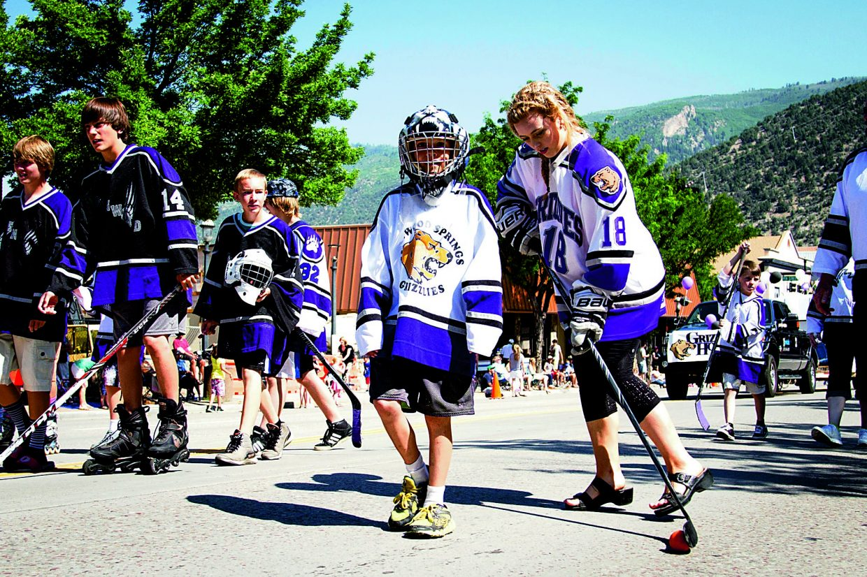 The Glenwood Springs Grizzly Hockey players and representivies make their way down Grand Ave during the Strawberry Days Parade.