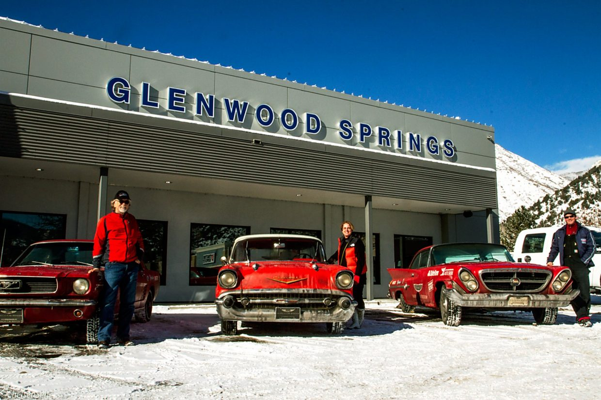 Vintage cars once used for State Farm claims calls stopped Thursday at Glenwood Springs Ford en route from LeMay — America's Car Museum in Tacoma, Washington, to Detroit for the upcoming North American International Auto Show. From left to right, three of the drivers — David L. Madeira, Valerie O'Shea and William Hall — stand beside the cars.