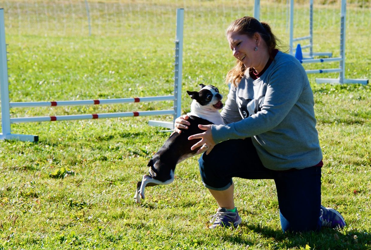 Shannon St. Antoine, from Bennett, Colo., praises her dog Lily during the DOCNA national championship competition on Friday at North Face Park in Carbondale.
