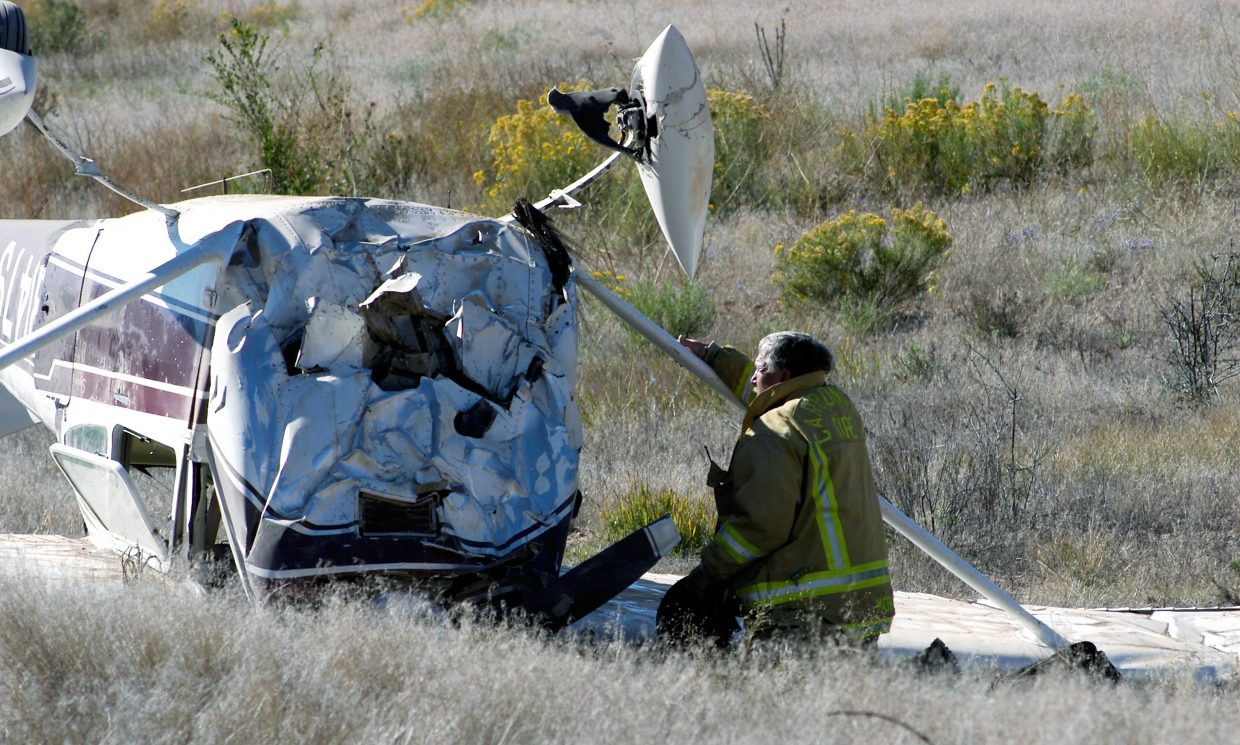 A firefighter inspects the damage to the nose of the Cessna 182G that crash-landed south of the Glenwood Springs Municipal Airport near Cattle Creek Sunday morning.