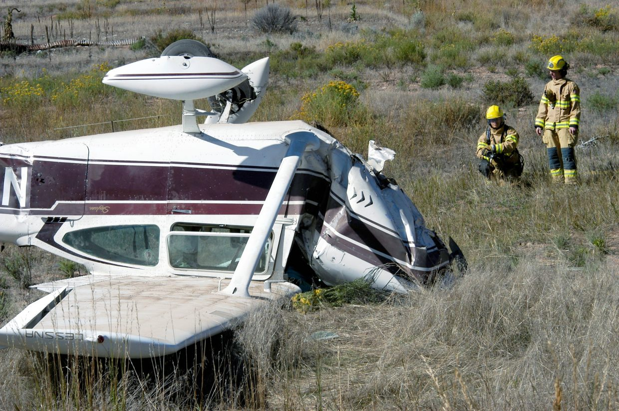 Firefighters inspect the damage after a small plane crashed next to the Rio Grande Trail near Cattle Creek Sunday morning. Two occupants of the plane were taken to Valley View Hospital with unspecified injuries.