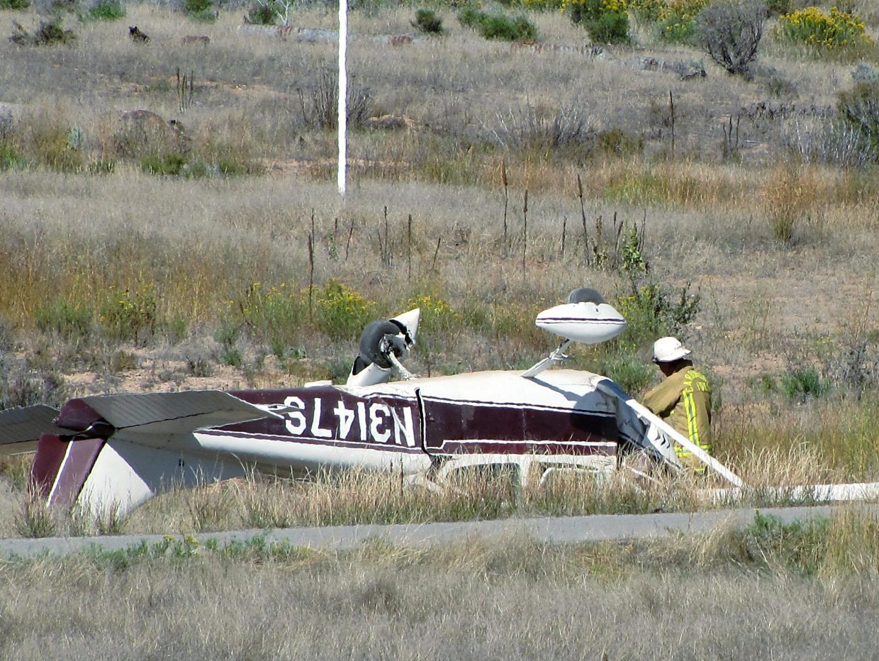 A firefighter Sunday examines the plane that crashed near Cattle Creek.