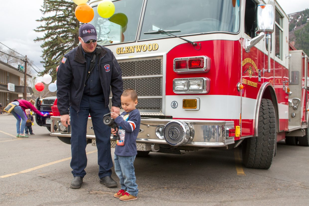 Four year old Elijah Montgomery and Jason Grosse of the Glenwood Springs fire deptarment at the fundraiser for the Children's Miracle Network hosted by Rite-Aid on Saturday afternoon.