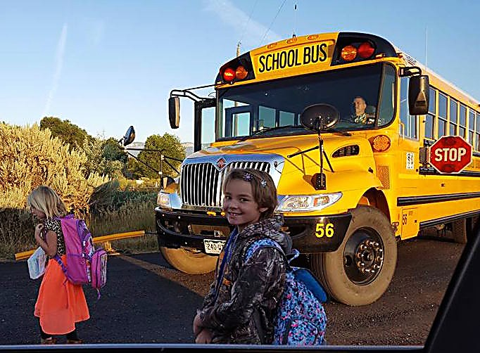 Kylee and Ariza Dominguez prepare to get on the bus to go to Highland Elementary School.