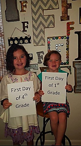 Madison, left, and Paislee Fields hold up signs before the first day of school at Highland Elementary School for the 2016-17 school year.