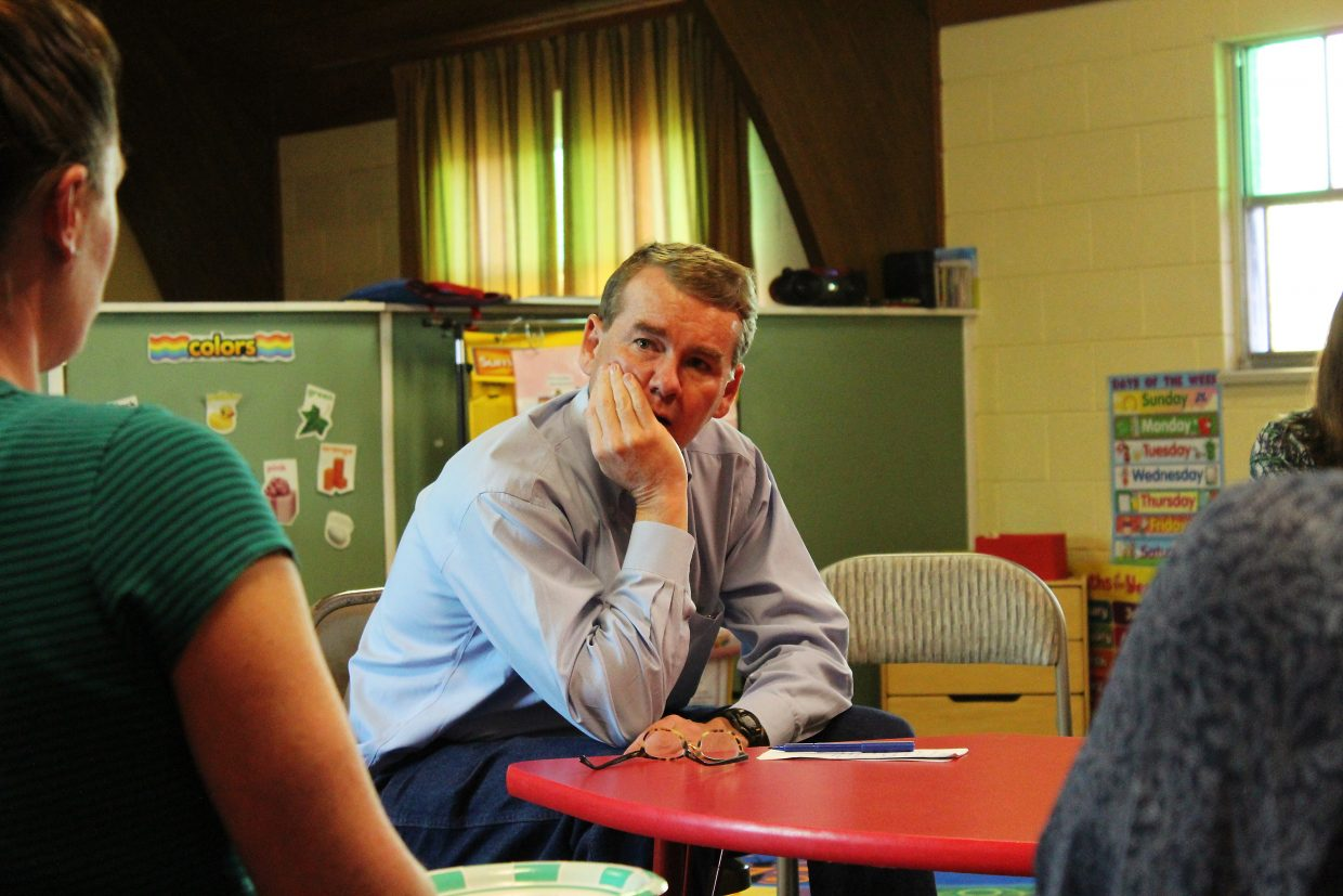 U.S. Sen. Michael Bennet listens as area mothers share some of the challenges they encounter regarding child care.