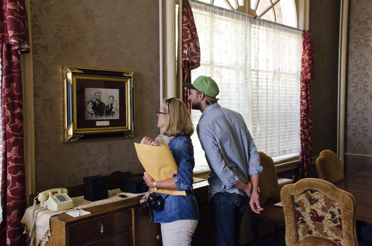 Barbara and Harris J. Bucklin examine a family photo in the hotel's Devereux suite.