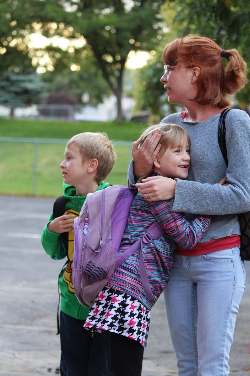Beaumarie Madden hugs her mother, Megan, as she and Nathaniel Madden, back, prepare for their first day of school at Bea Underwood Elementary School in Battlement Mesa.