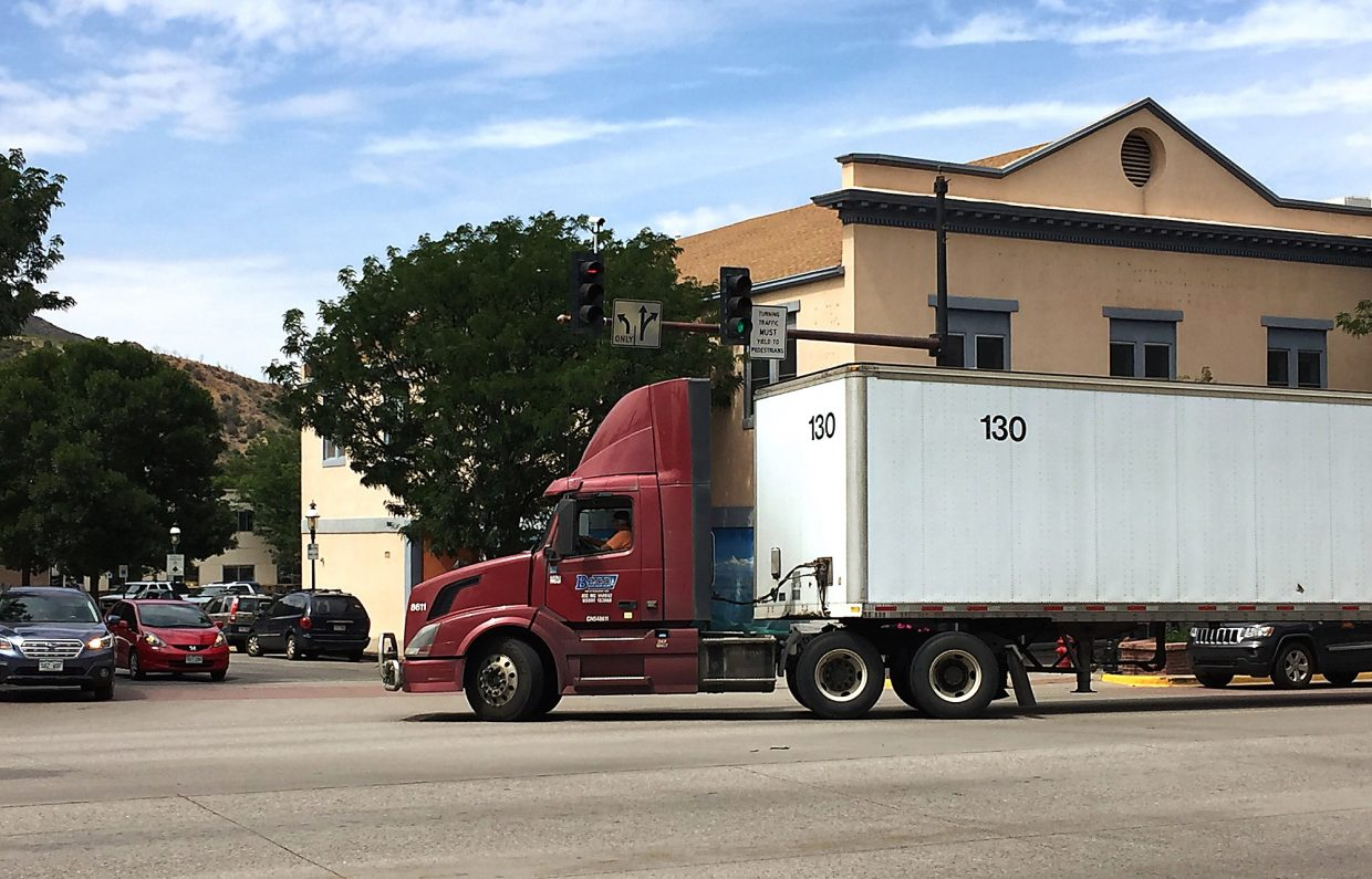 A contract postal delivery truck driver makes the usual sweeping righthand turn from Grand Avenue onto Ninth, en route to the U.S. Postal Service facility between Colorado and Pitkin, in the process forcing a motorist waiting to turn onto Grand to back out of the way.