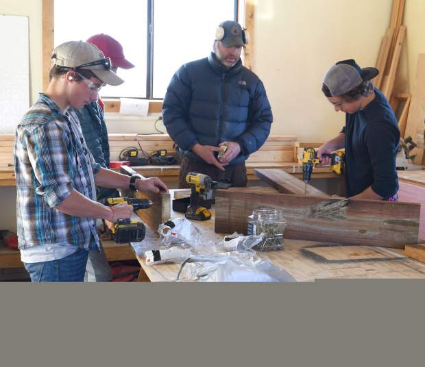 Colorado Rocky Mountain School students, from left, Elliot Ochsner, Dylan Webster and his father Damein Webster, and Nicco Dabrowski work to build a nesting platform as part of an osprey relocation project in Carbondale.
