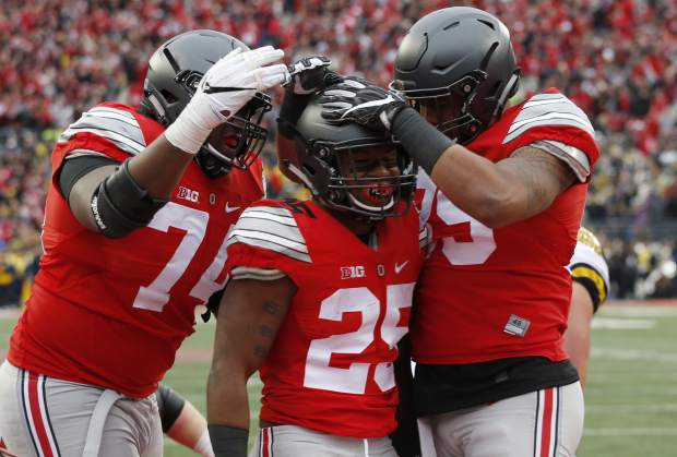 FILE - In this Nov. 26, 2016, file photo, Ohio State running back Mike Weber, center, celebrates his touchdown against Michigan with teammates Jamarco Jones, left, and Luke Farrell during the second half of an NCAA college football game in Columbus, Ohio. Alabama will play Washington and Ohio State is set to face Clemson in the College Football Playoff semifinals, announced Sunday, Dec. 4. (AP Photo/Jay LaPrete)