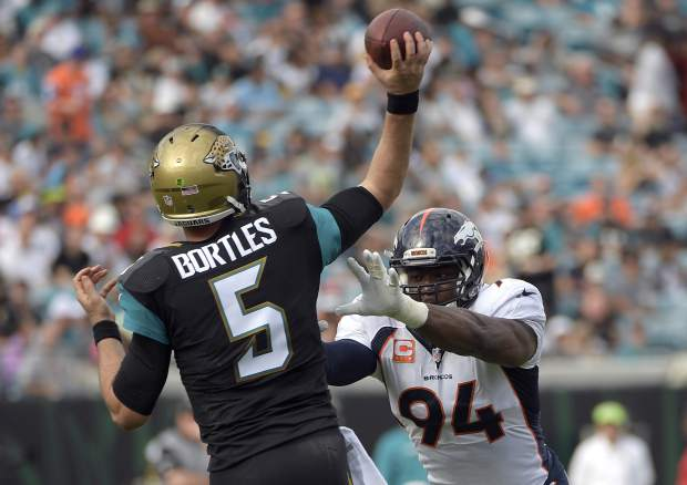 Jacksonville Jaguars quarterback Blake Bortles (5) throws a pass as he is pressured by Denver Broncos outside linebacker DeMarcus Ware (94) during the second half of an NFL football game in Jacksonville, Fla., Sunday, Dec. 4, 2016. (AP Photo/Phelan M. Ebenhack)