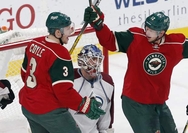 Minnesota Wild's Charlie Coyle, left, and Eric Staal celebrate Coyle's power play goal against Colorado Avalanche goalie Semyon Varlamov, center, of Russia during the first period of an NHL hockey game Tuesday, Dec. 20, 2016, in St. Paul, Minn. (AP Photo/Jim Mone)
