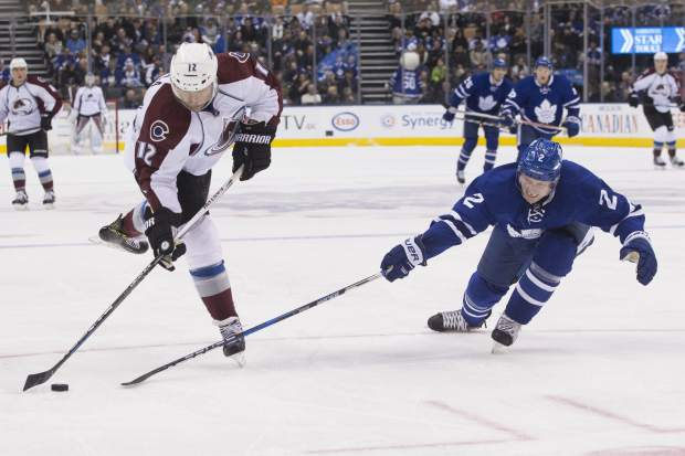 Colorado Avalanche right wing Jarome Iginla, left, shoots as Toronto Maple Leafs defenseman Matt Hunwick defends during first-period NHL hockey game action in Toronto, Sunday, Dec. 11, 2016. (Chris Young/The Canadian Press via AP)