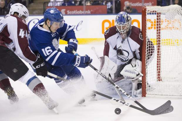 Colorado Avalanche goalie Semyon Varlamov, right, eyes the puck as Toronto Maple Leafs' Mitchell Marner, center, and Colorado Avalanche's Eric Gelinas, left, battle for possession during second period NHL hockey action in Toronto, on Sunday, Dec. 11, 2016 (Chris Young/The Canadian Press via AP)