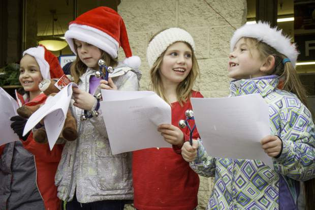 From right to left, Anaiah Mulligan, Selah Schneiter and Addi Jackson help lead Katina Leatherby's 2nd Grade class in Christmas carols and ringing bells for the Salvation Army at the Glenwood Springs City Market on Wednesday afternoon. Multiple classes from Glenwood Springs Elementary School took turns singing for the shoppers throughout the day.