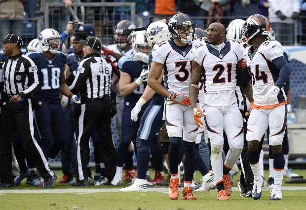 Denver Broncos cornerback Aqib Talib (21) walks to the bench with teammates Will Parks (34) and Justin Simmons (31) after Talib was involved in a scuffle with Tennessee Titans players in the first half of an NFL football game Sunday, Dec. 11, 2016, in Nashville, Tenn. (AP Photo/Mark Zaleski)