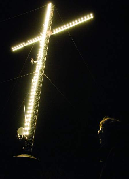 June Robinson looks at the view of Glenwood at night after turning on the switch to light the cross atop Red Mountain for the holiday season in a previous year.