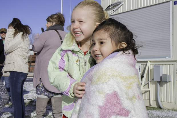 Friends McKinley Melendez, left, and Abril Molinda, 4, jump in excitement at the arrival of Santa and two of his elves who were flown to the E. Dene Moore Care Center by the Classic Air Medical helicopter on Saturday afternoon.