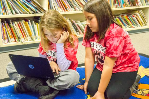 Glenwood Springs Elementary School fourth-graders Eva Marie Dietrich, left, and Jessenia Recio do research together on wolf populations and the effects they have on ranchers.