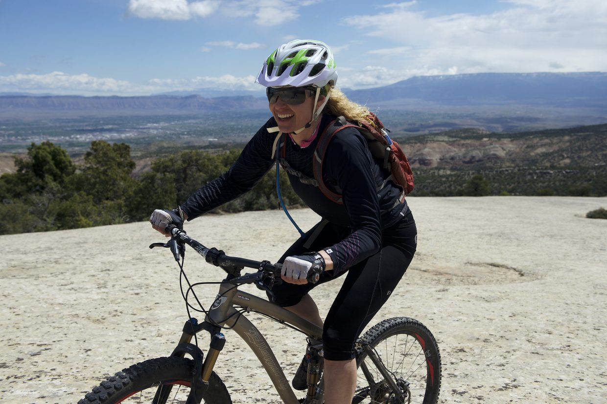 Host Shawna Henderson stops for a break after biking up one of dozens of trails in the Fruita area, now connected to nearby towns like Palisade and Grand Junction by a growing singletrack system spurred by longtime locals and bike shop owners.
