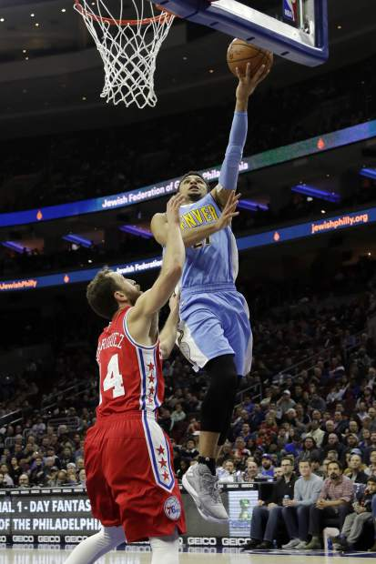 Denver Nuggets' Jamal Murray, right, goes up for a shot past Philadelphia 76ers' Sergio Rodriguez during the first half of an NBA basketball game, Monday, Dec. 5, 2016, in Philadelphia. (AP Photo/Matt Slocum)