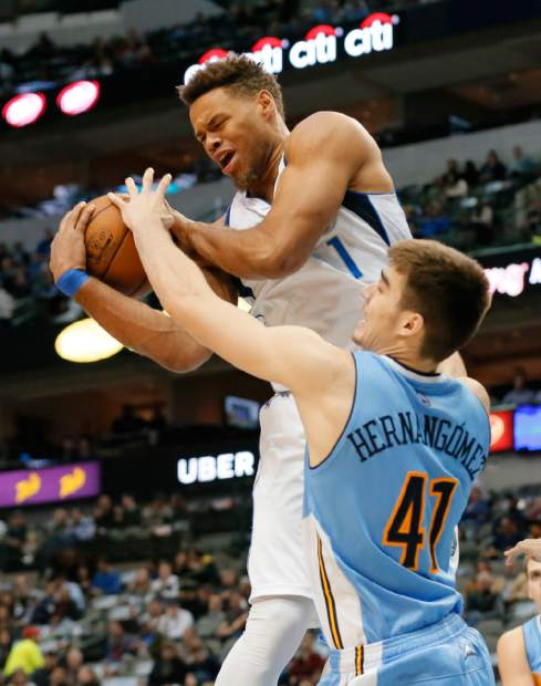 Dallas Mavericks' Justin Anderson grabs a defensive rebound over Denver Nuggets' Juancho Hernangomez (41) of Spain in the first half of an NBA basketball game, Monday, Dec. 12, 2016, in Dallas. (AP Photo/Tony Gutierrez)