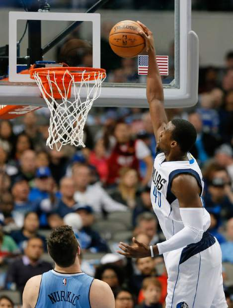 Denver Nuggets center Jusuf Nurkic of Bosnia Herzegovina looks up to see Dallas Mavericks' Harrison Barnes (40) dunk in the first half of an NBA basketball game, Monday, Dec. 12, 2016, in Dallas. (AP Photo/Tony Gutierrez)