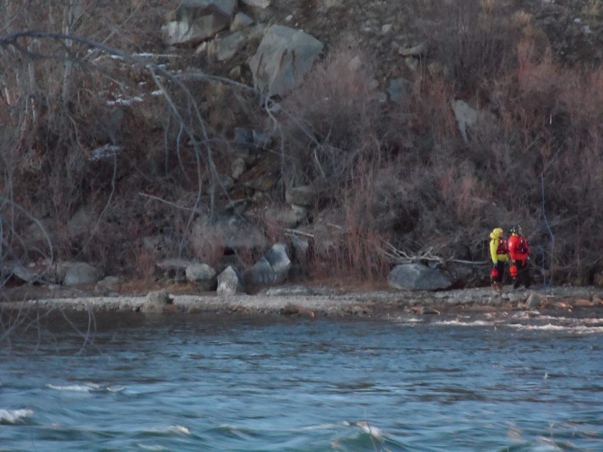 Rescuers work Saturday along the Colorado River bank near New Castle, where a body was found.