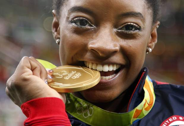 FILE - In this Aug. 11,2 016 file photo, United States' Simone Biles bites her gold medal for the artistic gymnastics women's individual all-around final at the 2016 Summer Olympics in Rio de Janeiro, Brazil. Briles was selected as the AP Female Athlete of the Year, on Monday, Dec. 26, 2016. (AP Photo/Dmitri Lovetsky, FIle_
