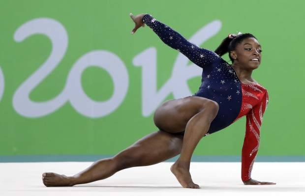 FILE - In this Aug. 7, 2016, file phot,o, United States' Simone Biles performs on the floor during the artistic gymnastics women's qualification at the 2016 Summer Olympics in Rio de Janeiro, Brazil. Briles was selected as the AP Female Athlete of the Year, on Monday, Dec. 26, 2016. (AP Photo/Rebecca Blackwell, File)