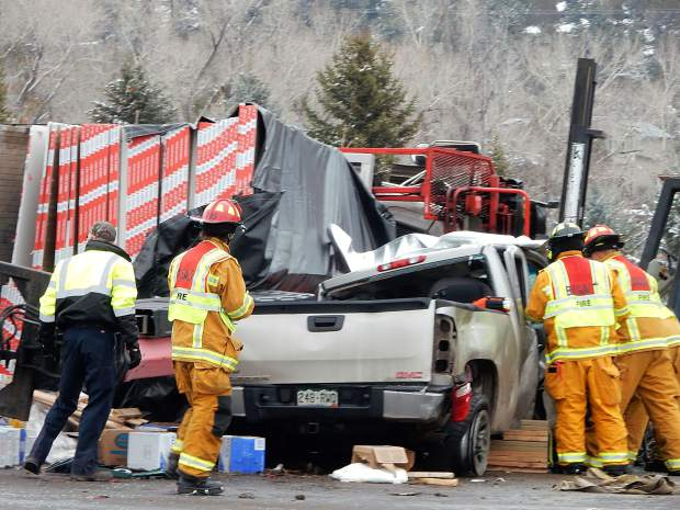 Basalt firefighters size up how to extricate the occupant of a pickup crushed Thursday afternoon by a pile of sheetrock.