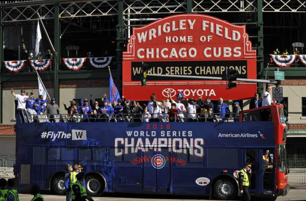 FILE - In this Nov. 4, 2016, file photo, a bus carrying Chicago Cubs players, family and friends passes Wrigley Field during a parade honoring the World Series champion baseball team in Chicago. The Cubs' first World Series title since 1908 is the runaway winner for top sports story of 2016. (AP Photo/Paul Beaty, File)